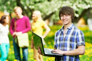 One young smiling happy student with laptop in front of young people group at spring outdoors